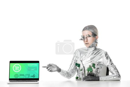 Photo for Silver robot sitting at table and pointing on laptop with shopping appliance isolated on white, future technology concept - Royalty Free Image