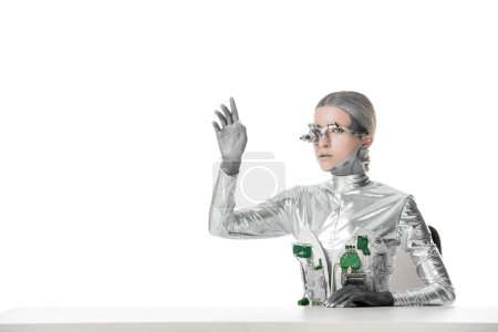 silver robot with eye prosthesis sitting at table and touching something isolated on white, future technology concept