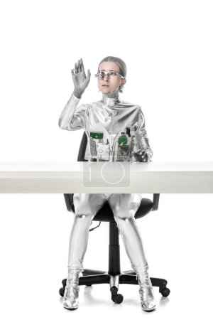 cyborg sitting at table and touching something isolated on white, future technology concept