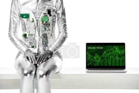 cropped image of robot sitting on table near laptop with online trade appliance isolated on white, future technology concept