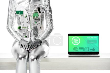 cropped image of robot sitting on table near laptop with shopping appliance isolated on white, future technology concept