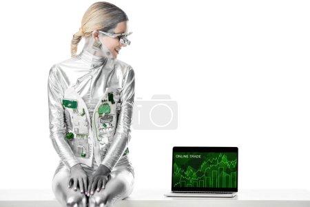 Foto de Sonriente robot plata sentado en la mesa y mirando portátil con aparato de comercio online aislado en concepto de blanco, futuro de la tecnología - Imagen libre de derechos