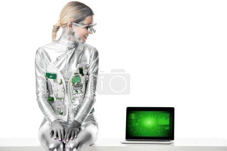 Foto de Sonriente robot plata sentado en la mesa y mirando portátil con dispositivo de negocios aislado en concepto de blanco, futuro de la tecnología - Imagen libre de derechos