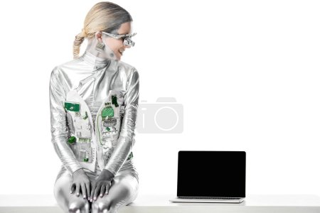 Photo for Smiling silver robot sitting on table and looking at laptop with blank screen isolated on white, future technology concept - Royalty Free Image