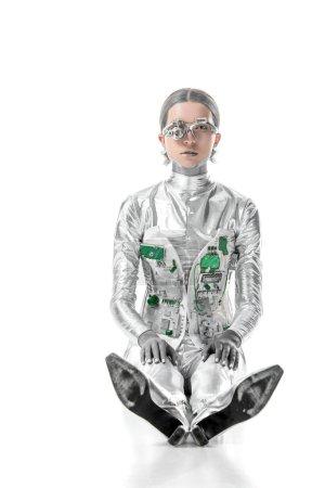 Foto de Plata robot sentado y mirando a cámara aislada en concepto de blanco, futuro de la tecnología - Imagen libre de derechos
