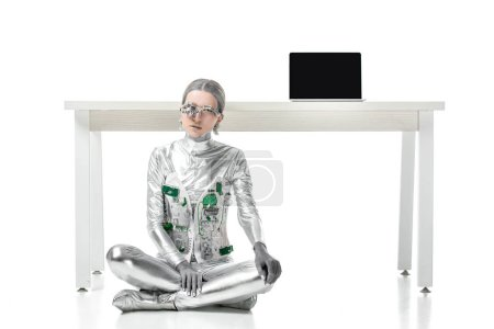 silver robot sitting near table with laptop isolated on white, future technology concept