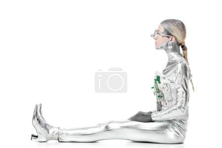 Foto de Vista lateral del robot plata sentado y mirando a aislado en concepto de blanco, futuro de la tecnología - Imagen libre de derechos