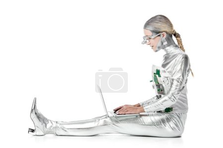 side view of silver robot sitting and using laptop isolated on white, future technology concept