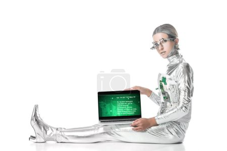 silver robot sitting and showing laptop with medical appliance isolated on white, future technology concept