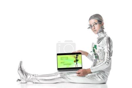 Foto de Plata robot sentado y mostrando portátil con mejores tiendas aparato aislado en concepto de blanco, futuro de la tecnología - Imagen libre de derechos