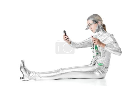 silver robot sitting with lipstick and looking at mirror isolated on white, future technology concept