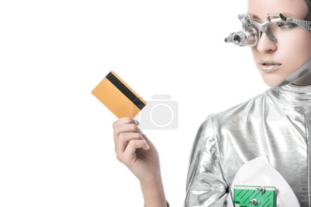 silver robot looking at credit card isolated on white, future technology concept
