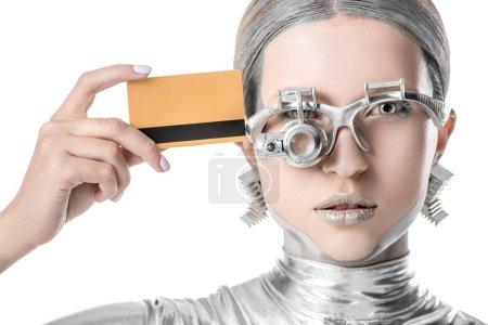 Photo pour Robot argent toucher la tête avec carte de crédit et regardant la caméra isolée sur concept technologique blanc, futur - image libre de droit