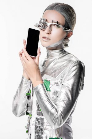 silver robot holding smartphone with blank screen and looking at camera isolated on white, future technology concept