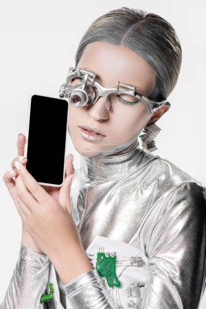 Photo pour Robot argenté tenant smartphone avec écran blanc isolé sur blanc, concept technologique futur - image libre de droit