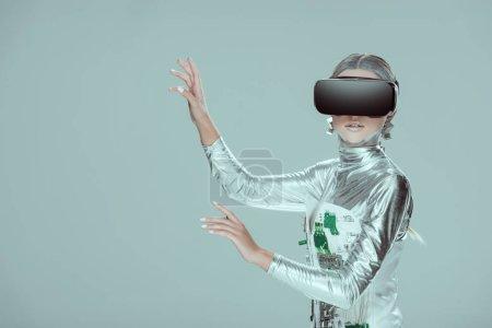 Foto de Robot plateado algo tocando con el casco de realidad virtual aislado en concepto de la tecnología futura gris - Imagen libre de derechos