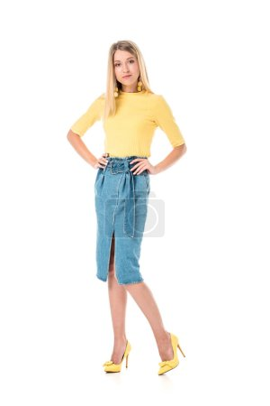 confident attractive woman in yellow shirt standing with hands akimbo and looking at camera isolated on white