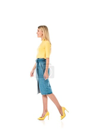 side view of attractive woman in yellow shirt and denim skirt walking isolated on white