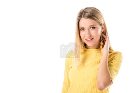 Photo for Smiling attractive woman in yellow shirt touching neck and looking at camera isolated on white - Royalty Free Image