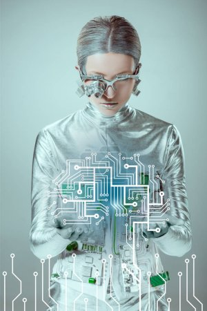 futuristic silver cyborg looking at circuit board isolated on grey, future technology concept