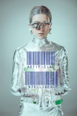 futuristic silver cyborg with barcodes and artificial intelligence in hands looking at camera isolated on grey, future technology concept