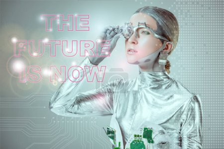 Photo pour Futuriste cyborg argent ajuster les prothèses oculaires et en regardant « the future is now » lettrage isolés sur gris avec des données numériques, concept technologique futur - image libre de droit