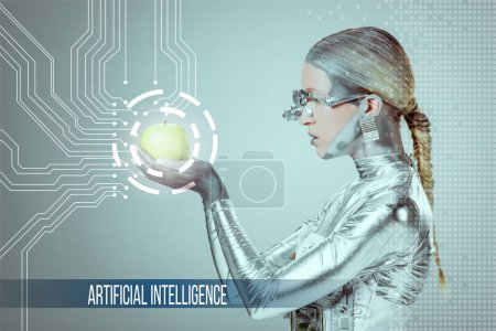 """Photo for Side view of cyborg holding and examining green apple with digital data isolated on grey with """"artificial intelligence"""" lettering - Royalty Free Image"""
