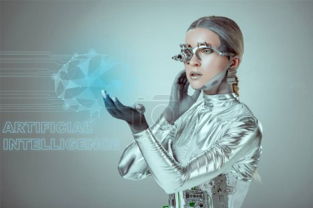 "futuristic silver cyborg touching digital data with ""artificial intelligence"" lettering isolated on grey, future technology concept"