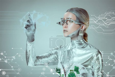 Foto de Cyborg plata futurista gesticulando con la mano y mirando datos digitales aislados en concepto de la tecnología futura gris - Imagen libre de derechos