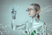 futuristic silver cyborg gesturing with hand and looking at digital data isolated on grey, future technology concept