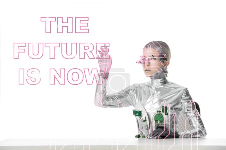 "Photo for Silver cyborg with eye prosthesis sitting at table and touching ""the future is now"" lettering isolated on white, future technology concept - Royalty Free Image"