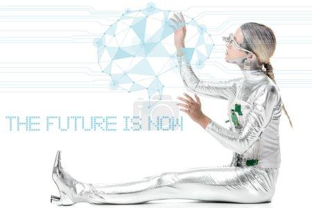 """Foto de Lateral de cyborg plata sentado y tocando datos digitales aislados en blanco con """"el futuro es ahora"""" Letras - Imagen libre de derechos"""