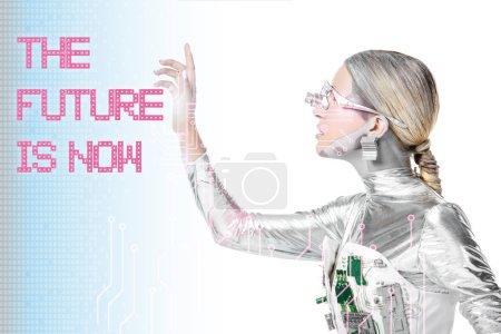 """Photo pour Vue latérale du cyborg argenté touchant """"l'avenir est maintenant"""" lettrage isolé sur blanc avec des données numériques - image libre de droit"""
