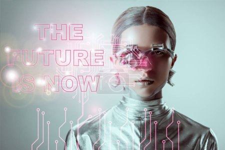 "futuristic silver cyborg on grey with ""the future is now"" lettering and digital data"