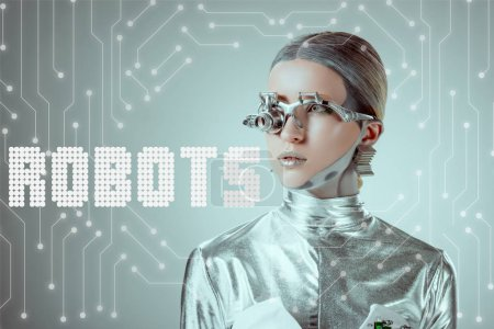 "futuristic silver cyborg looking away isolated on grey with ""robots"" lettering and digital data"