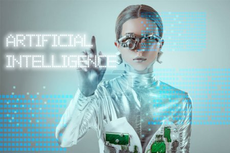 "Photo for Futuristic silver cyborg touching ""artificial intelligence"" lettering on grey with digital data - Royalty Free Image"