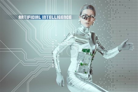 "Photo for Silver cyborg walking and looking at camera on grey with ""artificial intelligence"" lettering and digital data - Royalty Free Image"