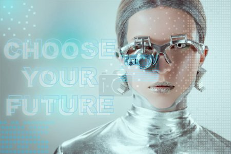 """close-up view of silver robot with eye prosthesis looking at camera on grey with """"choose your future"""" lettering and digital data"""