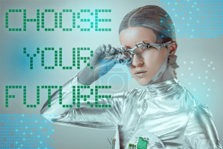 """futuristic silver cyborg adjusting eye prosthesis and looking at camera on grey with """"choose your future"""" lettering"""