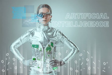 "Photo for Futuristic silver cyborg standing with hands on waist and looking at camera on grey with ""artificial intelligence"" lettering and digital data - Royalty Free Image"