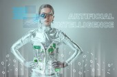 "futuristic silver cyborg standing with hands on waist and looking at camera on grey with ""artificial intelligence"" lettering and digital data"
