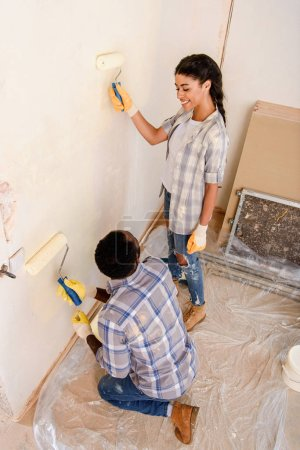 high angle view of happy young couple painting wall during renovation of home