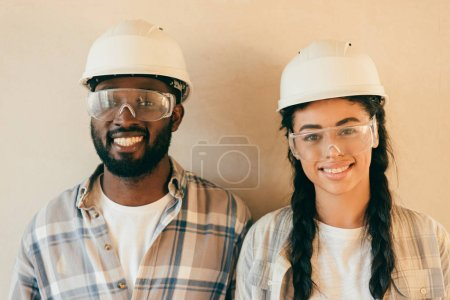 happy young couple in safety helmets and eyeglasses looking at camera renovation of home