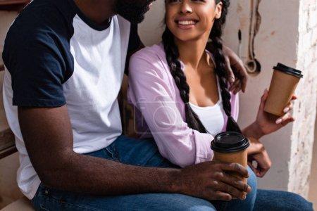 Photo pour Gros plan du couple souriant, assis dans les escaliers avec des gobelets en papier de café pendant la rénovation de la maison - image libre de droit
