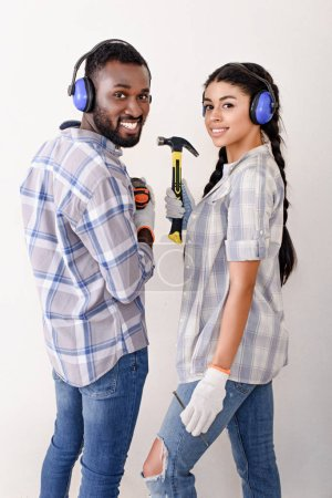 happy young couple with protective headphones and tools looking at camera while making renovation of home