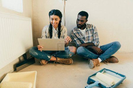Couple sitting on floor and using laptop during renovation of home