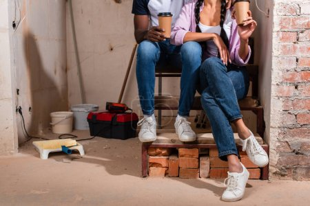cropped shot of couple sitting on stairs with paper cups of coffee during renovation
