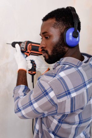 handsome young man in protective headphones drilling wall