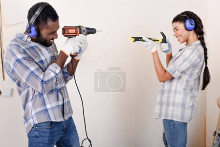 side view of playful couple having fun with hammer and drill while making renovation of home