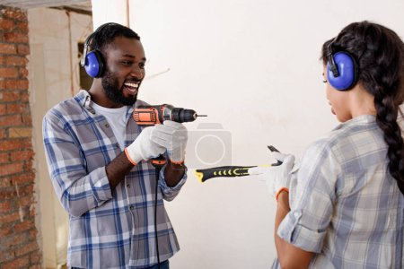 playful couple having fun with hammer and drill while making renovation of home